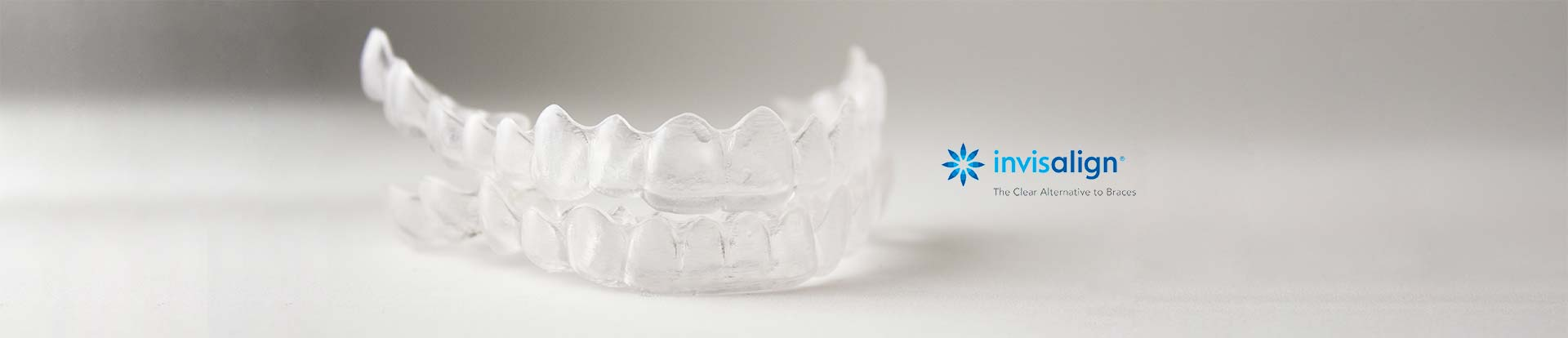 The photo of invisalign braces on the grey background.
