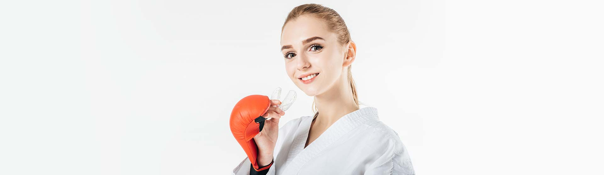 Smilling female karate fighter holding mouthguard.