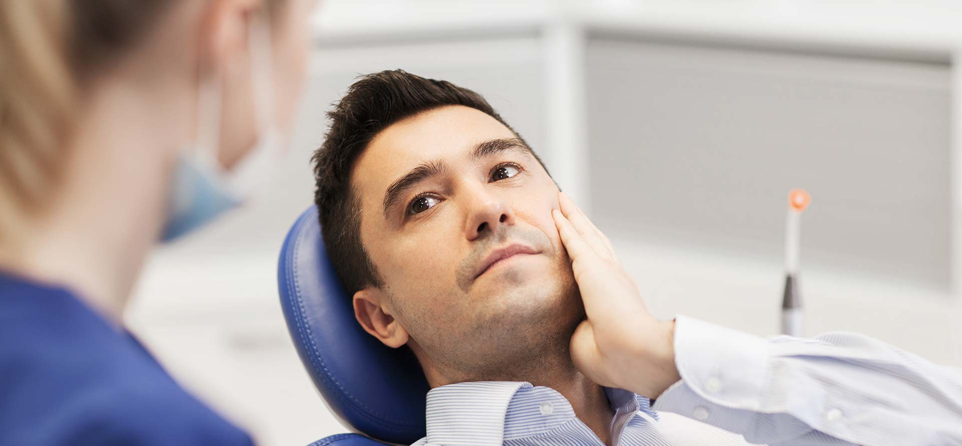 Man with tooth pain sitting on a dental chair.